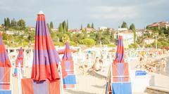 Adriatic beach with red umbrellas Stock Photos