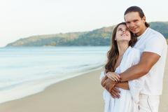 Romantic couple walking on romantic travel honeymoon vacation at the beach Stock Photos