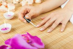 Woman is making french manicure herself Stock Photos