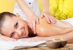 Beautiful smiling woman getting a massage in the spa salon Stock Photos