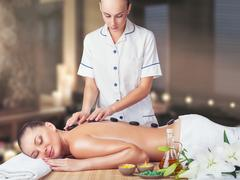 A beautiful young woman with her eyes closed getting a massage at the spa Stock Photos