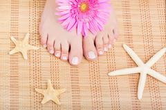 Close-up of beautiful manicured feet with a pedicure, flower and starfish Stock Photos