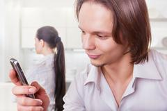 Young couple after quarrel. Man looking with a smile on your phone in the foregr Stock Photos