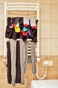 Socks and leggings drying on bathroom radiator Stock Photos