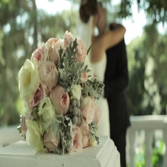 Bride's bouquet and kissing married couple on the background. Stock Footage
