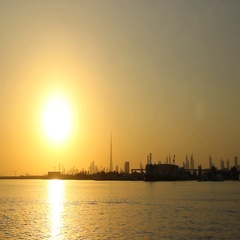 Dubai sunset, Creek Harbour water, golden low sun glow ahead, cityscape contour Stock Footage