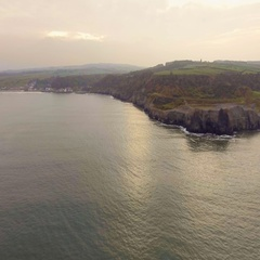 Fly towards Britain mainland through vast sea, coast rocks, aerial view Stock Footage