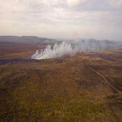 Burning fields in the hills, panning shot. Aerial view Stock Footage