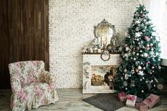 Christmas tree and fireplace with an armchair Stock Photos