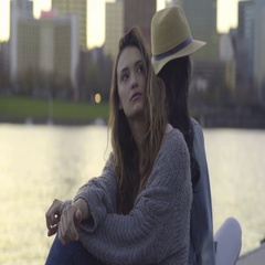 Young Women Sit Back To Back On A Dock And Relax, Enjoy Sunset In City Stock Footage