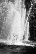 Vertical black and white fountain splashes background Stock Photos