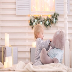 Baby in Santa hat sits near a Christmas tree with a gift Stock Footage