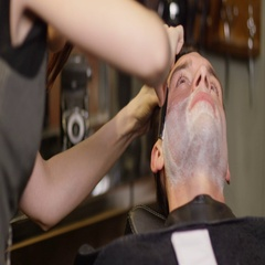 4K Close up of man getting a shave with razor in traditional barber shop Stock Footage