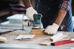 Worker grinds the wood of angular grinding machine Stock Photos