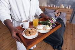 African man holding the tray with breakfast in bedroom Stock Photos