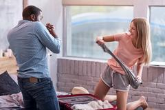 Smiling couple fighting with clothes while packing for the journey Stock Photos
