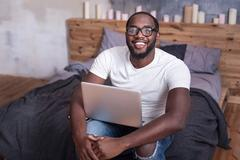 Joyful man holding laptop in bedroom Stock Photos
