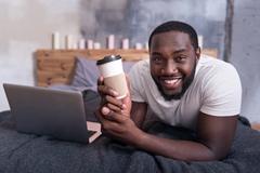 Joyful man holding cup of coffee in bedroom Stock Photos