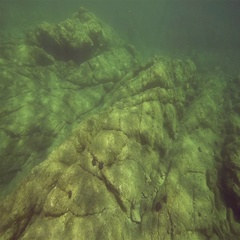 Underwater volcanic rock in the sea lit by the rays Stock Footage