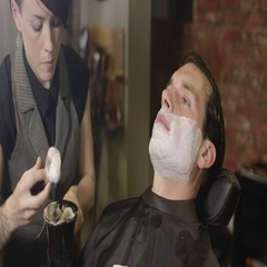 4K Close up of man being prepared for a traditional shave with a razor in barber Stock Footage