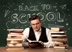 A young ambitious teacher in glasses sitting at classroom desk with pile of book Stock Photos