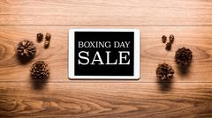 Magical Boxing Day Sale theme background, pine cones and digital table Stock Photos