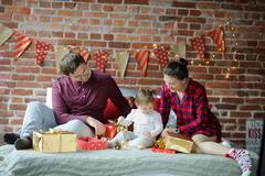 Young family gathers to decorate the room and wraps Christmas presents. Stock Photos