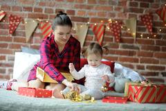 Young woman and her little daughter with delight look at gifts. Stock Photos