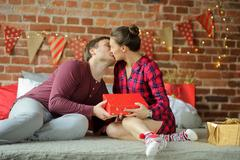 Family congratulating each other a gentle kiss, they exchange Christmas gifts. Stock Photos