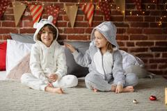 Brother and sister  sit on a bed and expect Christmas gifts. Stock Photos