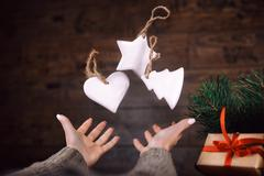 Woman hands throws up homemade Christmas tree toys. dark background. Selective Stock Photos