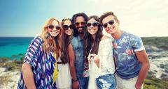 Happy hippie friends with selfie stick on beach Stock Photos
