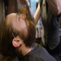 4K Female barber giving customer a beard trim in traditional retro barber shop Stock Footage