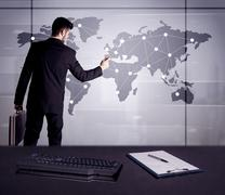 A young office worker drawing on world map and connecting dots with lines, prese Stock Photos