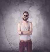 Funny vintage guy with long beard and stylish hair standing in front of urban co Stock Photos