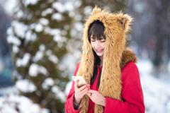 Woman outdoors with cellphone in wintertime Stock Photos