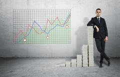Businessman standing in confident pose leaning on stack of stocks Stock Photos