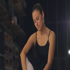 Slim ballerina in a black corset and black tutu tying pointe shoes. Classical Stock Footage