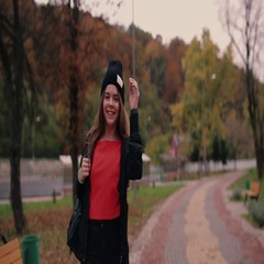 Girl with a long hair, black hat and backpack runs cross the urban autumn park Stock Footage