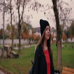 Beautiful girl in a modern fashionable look slowly wonders in the city park Stock Footage