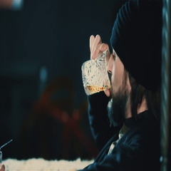 Young bearded man drink alcohol at bar HD slow motion video. Guy hat whiskey Stock Footage
