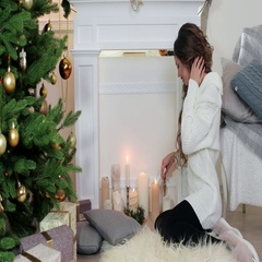 Christmas, girl lights a candle sitting by the fireplace near the Christmas tree Stock Footage