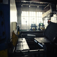 Wide sheets of metal are braided in big rolls at plant, time lapse Stock Footage