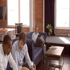 Businessmen Working On Sofas In Relaxation Area Of Office Stock Footage