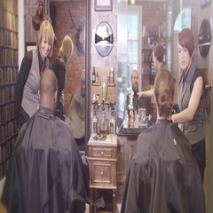 4K Friendly female stylists working on clients in traditional retro barber shop Stock Footage
