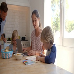 Kids working at kitchen table with mum, while dad cooks Stock Footage
