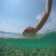 HALF UNDERWATER SLOW MOTION: Unrecognizable person scooping crystal clear water Stock Footage