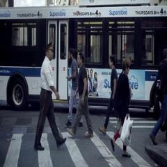 Doorman and people crossing street bus UPS truck and cars taxi cabs NYC Stock Footage