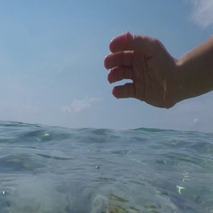 SLOW MOTION SPLIT UNDERWATER: Hand scooping water, drops falling on sea surface Stock Footage