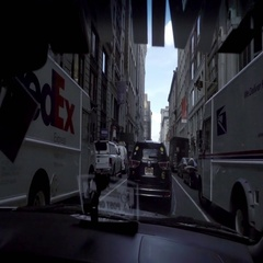 FedEx and USPS postal delivery trucks driving past on street in NYC Stock Footage